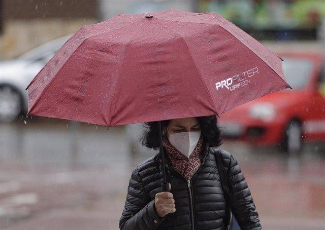 Transeúntes protegidos con mascarilla y un paraguas caminan por las calles de la capital un día marcado por la llegada a la península de una borrasca fría que ha activado la alerta por viento o lluvia en 8 comunidades. En Madrid, a 15 de abril de 2020.