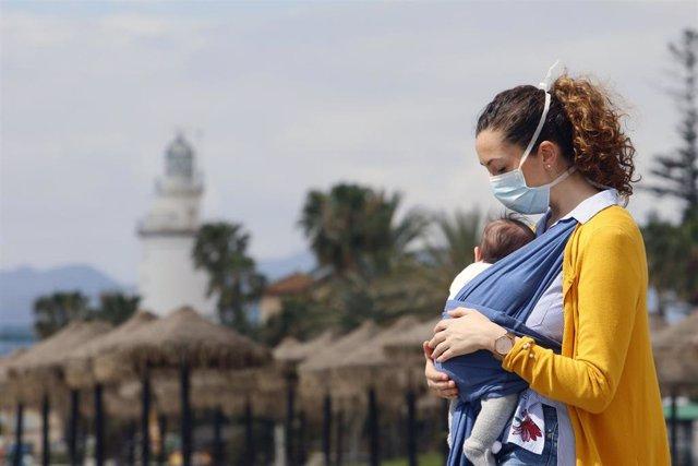 Una mujer protegida con una mascarilla da un paseo con su bebé en la playa de La Malagueta el primer día en el que los menores de 14 años pueden salir, en Málaga (Andalucía ,España) a 26 de abril de 2020.
