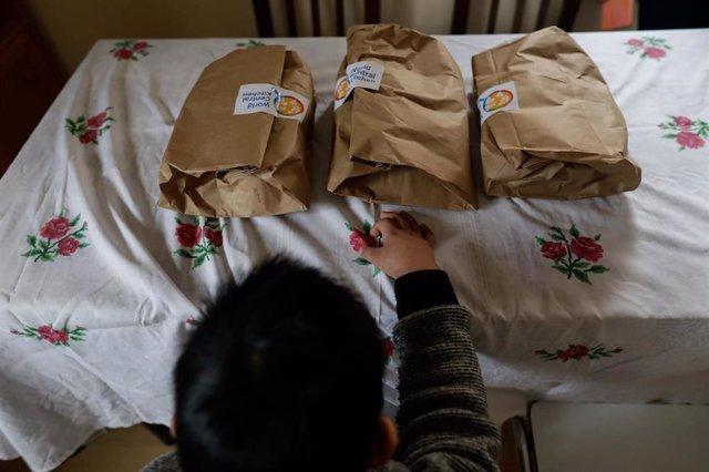 Un niño durante la comida en su casa del barrio madrileño de Carabanchel momentos antes de abrir el menú de la ONG del chef José Andrés, que reparte en Madrid a las familias más necesitadas durante el estado de alarma provocado por el coronavirus, en Madr