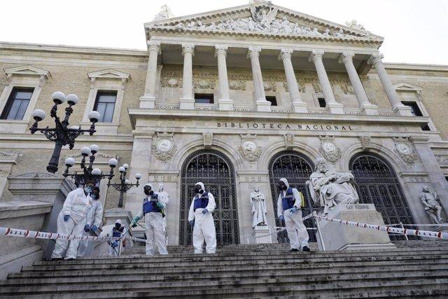 Agentes de la UME con mochilas nebulizadoras en la desinfección de las escaleras de la entrada de la Biblioteca Nacional