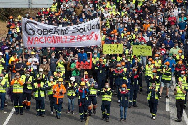 Participantes protegidos con mascarilla sujetan pancartas durante la manifestación del comité de empresa de Alcoa entre la factoría y la localidad de San Cibrao a 2 de junio de 2020.