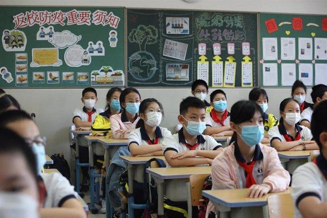 Estudiantes con mascarilla en una escuela de Pekín