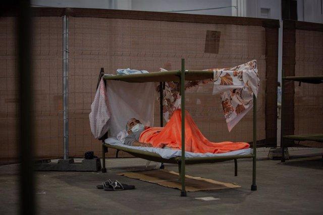 Un hombre descansa en su cama en el interior de las instalaciones del albergue de Fira Barcelona, habilitado por la crisis de la pandemia del coronavirus para 225 personas sin techo. En Barcelona, Catalunya (España), a 28 de mayo de 2020.