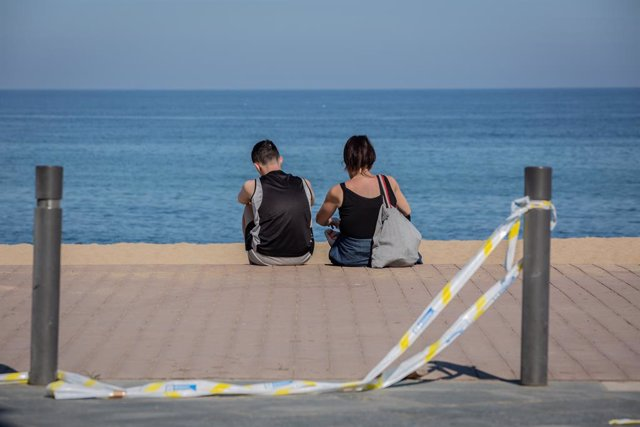 Dos joves asseguts en el Passeig Marítim de la Platja de la Barceloneta durant el dia 66 de l'estat d'alarma decretat pel Govern a causa del Covid-19.