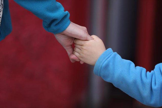 Un niño camina de la mano de un adulto. En Madrid (España) a 27 de abril de 2020.