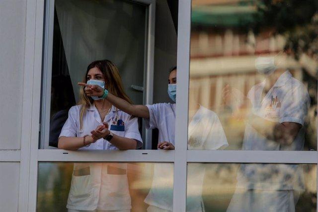 Sanitarios aplauden desde una ventana de del Hospital Fundación Jiménez Díaz cuando en la Fase 1 de la desescalada continúan los aplausos en homenaje a los profesionales sanitarios y demás sectores que han sido esenciales durante la pandemia del coronavir