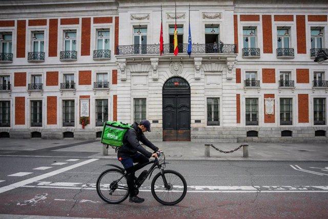 Un 'rider' de Uber Eats circula por la Puerta del Sol, en Madrid (España) a 19 de abril de 2020.