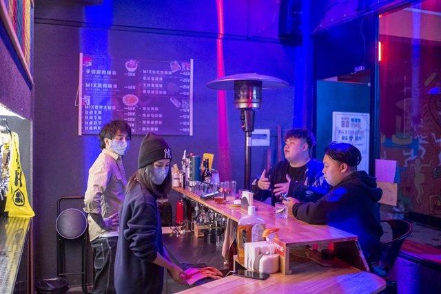 Camareros y clientes de un bar de la ciudad en el sur de China de Nanning, donde sólo se han registrado 16 casos de la COVID-19 en una población de siete millones de personas.