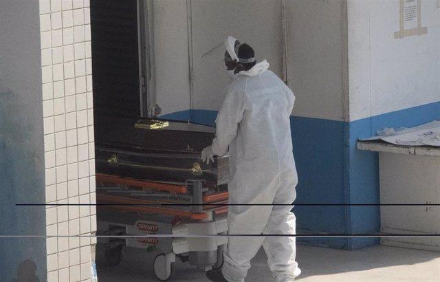 Un trabajador sanitario llevando un féretro dentro de una clínica en Río de Janeiro