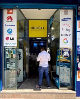 Un hombre espera frente a un distribuidor autorizado de la compañía de telecomunicaciones MásMóvil en Madrid