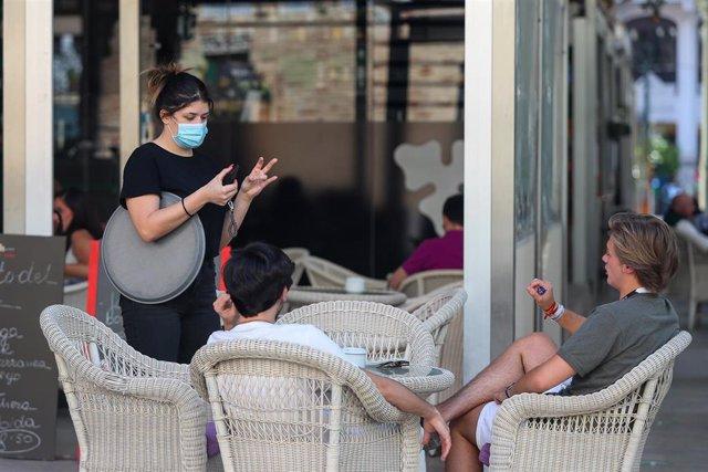 Varias personas piden consumiciones en una terraza en el Mercado de Colón durante la fase 2 de la desescalada en la pandemia de coronavirus COVID19.