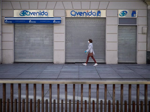 Una mujer con mascarilla pasa junto a una perfumería que aún permanece cerrada al público durante el segundo día de la fase 0 de la desescalada en la que se permite la apertura con limitaciones de algunos establecimientos, en Pamplona/Navarra (España) a 5