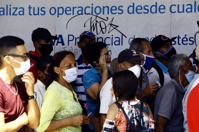 Colas para entrar en un banco de la ciudad venezolana de Valencia durante la pandemia de coronavirus