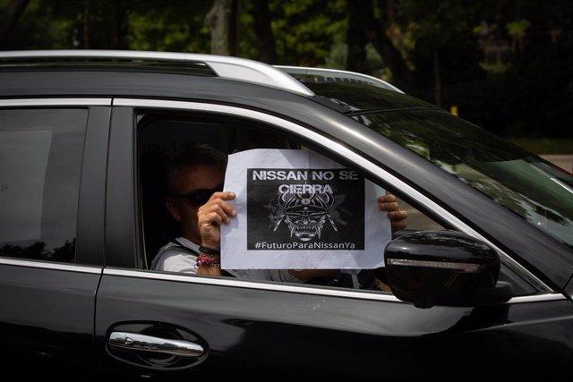 Una trabajadora de Nissan Motor Ibérica, en la Zona Franca de Barcelona, sujeta un papel desde su coche en el que se lee 'Nissan no se cierra', durante la congregación de trabajadores a su paso por la Avenida Diagonal en una de las marchas lentas que se h