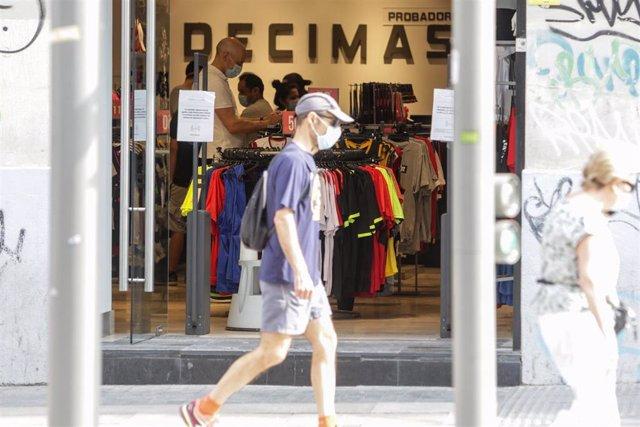 Un hombre protegido con mascarilla pasa junto a una tienda Décimas abierta durante la fase 1 de la desescalada en la que se permite reapertura de locales y establecimientos minoristas con una superficie igual o inferior a 400 metros cuadrados.