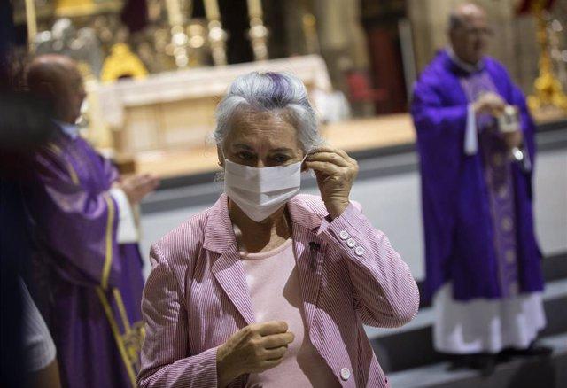 Una mujer se coloca la mascarilla tras comulgar en el funeral en recuerdo y homenaje a las víctimas del coronavirus. En la Catedral.(Sevilla, Andalucía, España), a 04 de junio de 2020.