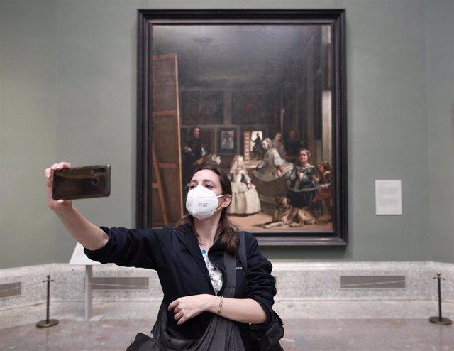 Una persona protegida con mascarilla se realiza una fotografía con una obra durante la presentación de la reapertura del Museo del Prado