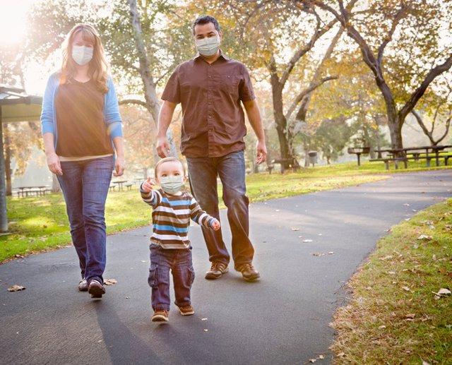 Familia con mascarilla en el parque.