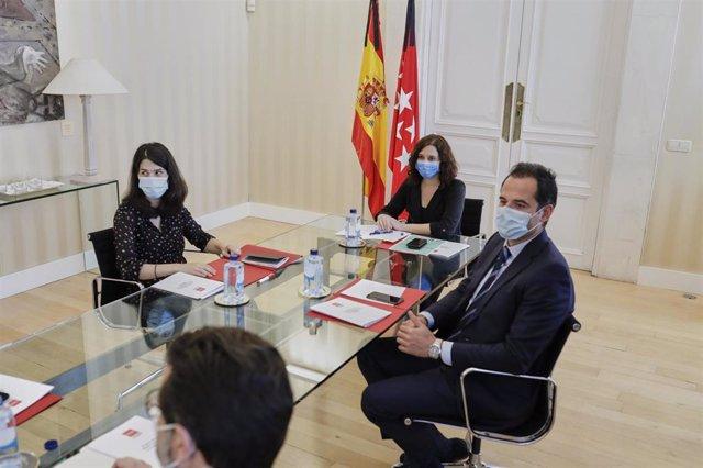 La presidenta de la Comunidad de Madrid, Isabel Díaz Ayuso (2d) el vicepresidente, Ignacio Aguado (1d), el consejero de Hacienda, Javier Fernández-Lasquetty (2i), se reúnen con la portavoz de Unidas Podemos en la Asamblea de Madrid, Isa Serra (1i).