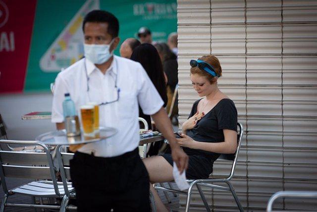 Un cambrer serveix en la terrassa d'un bar durant el segon dia de la reobertura al públic de les terrasses, Catalunya (Espanya) a 26 de maig de 2020.