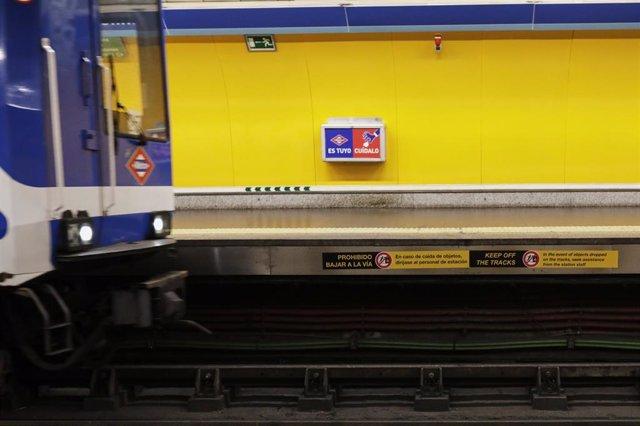 Un tren de metro entra en una estación en la que se ve uno de los carteles que la Comunidad de Madrid ha instalado a lo largo del borde del andén en las estaciones del Metro de Madrid.