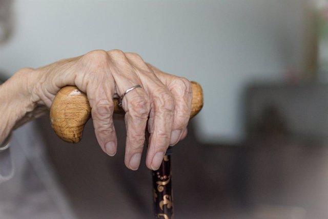 Mà d'una anciana amb bastó en una imatge d'arxiu.