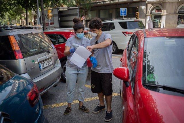 Dos voluntaris de l'ONG Proactiva Open Arms parlen abans de realitzar una entrega de material sanitari en plena crisi del Covid-19. A Barcelona, Catalunya, (Espanya), a 8 de maig de 2020.