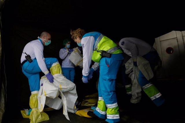 Sanitarios del SUMMA se visten con material protector frente al Covid-19 antes de entrar en el hospital temporal de IFEMA para trasladar a un paciente de la UVI de IFEMA al Hospital Puerta de Hierro, durante un día de trabajo del Servicio de Urgencia Médi