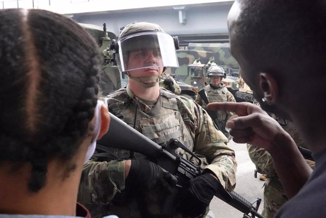 Manifestantes negros protestando frente a un militar de la Guardia Nacional