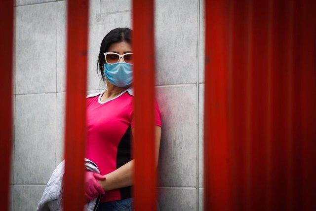 Una mujer por mascarilla por el coronavirus en Quito.