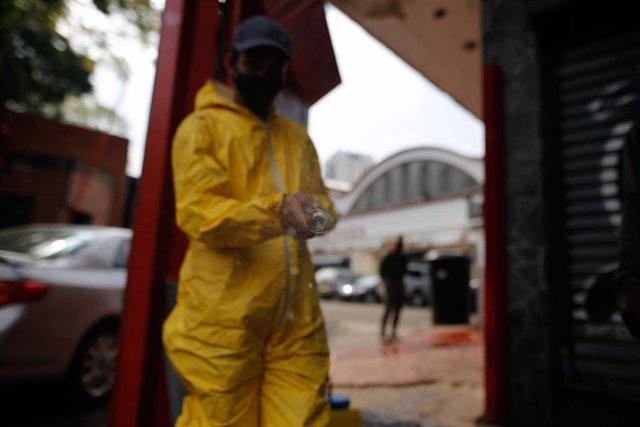 Un trabajador desinfectando la entrada a un mercado por el coronavirus.