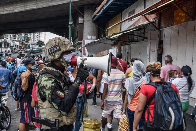 Un agente venezolano transmite en una calle de Caracas las medidas a seguir para prevenir el contagio del coronavirus