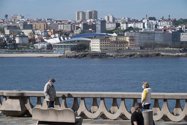 Dos personas pasean por el paseo marítimo de A Coruña (Galicia), con el estadio de Riazor de fondo, en el segundo día en que el Gobierno permite salir a hacer deporte de forma individual y pasear con otra persona con la que se conviva, a determinadas hora