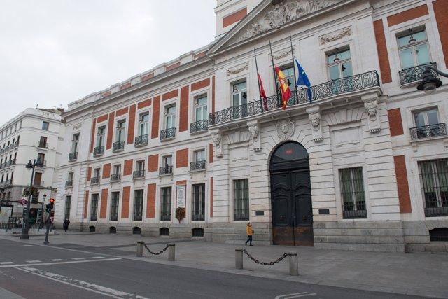 Fachada del la Real Casa de Correos, sede de la Comunidad de Madrid, con las banderas a medio asta durante el minuto de silencio en el primer día del luto oficial por los fallecidos del COVID-19.