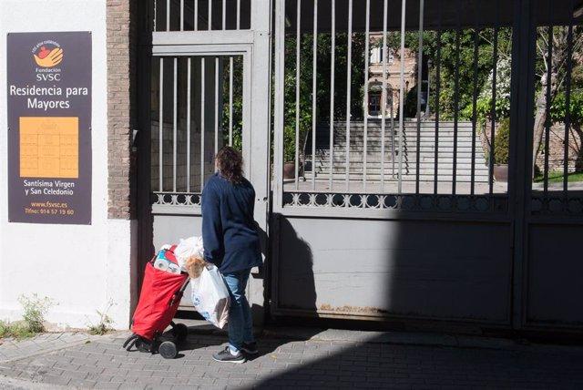 Una trabajadora protegida con mascarilla entra por la puerta de la Residencia Santísima Virgen y San Celedonio donde hasta la fecha han fallecido ya 23 personas y 35 empleados (37 de ellos sanitarios) están de baja, en Madrid (España), a 26 de marzo de 20