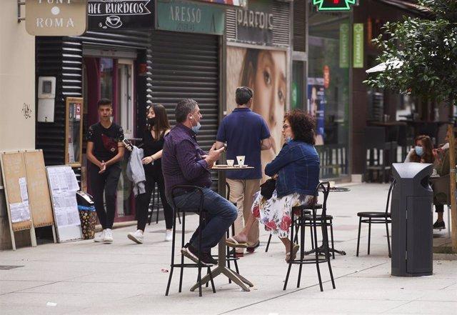 Dos personas disfrutan en una terraza en una imagen de archivo