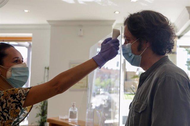 Una dependiente toma la temperatura a un cliente en la Inmobiliaria Gilmar en la localidad madrileña de Boadilla del Monte (Glorieta Virgen María, 7,)