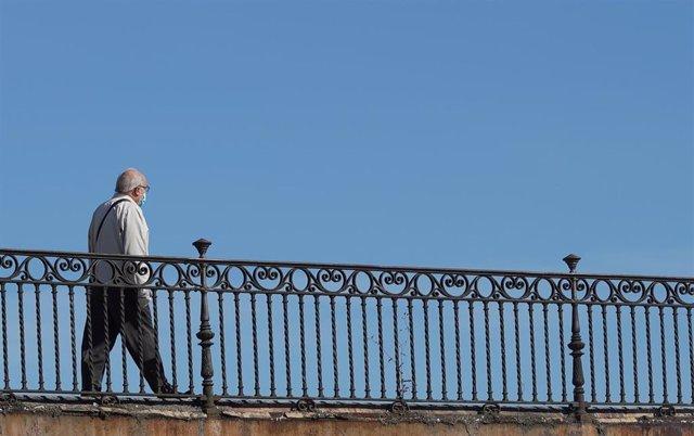 Persona mayor protegido con mascarilla pasea por el puente de Triana.