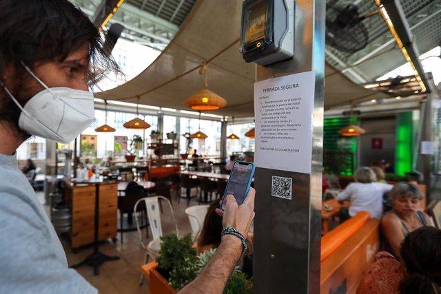 Una persona consulta la carta de productos con código QR en un bar de el Mercado de Colón durante la fase 2 de la desescalada en la pandemia de coronavirus COVID19. En Valencia, España, a 3 de junio de 2020.