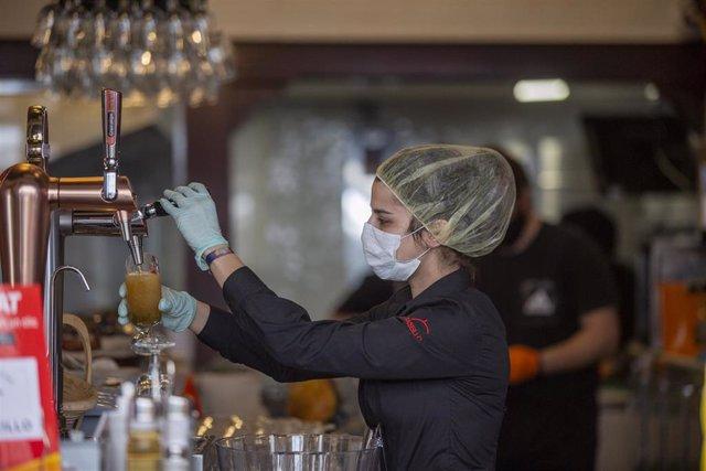Una empleada de un bar sirve una cerveza el día en el que Sevilla pasa a la fase 1 del plan de desescalada.