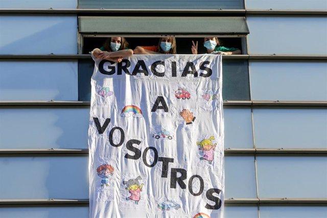 Tres sanitarias del Hospital General Universitario Gregorio Marañón en una ventana del hospital.