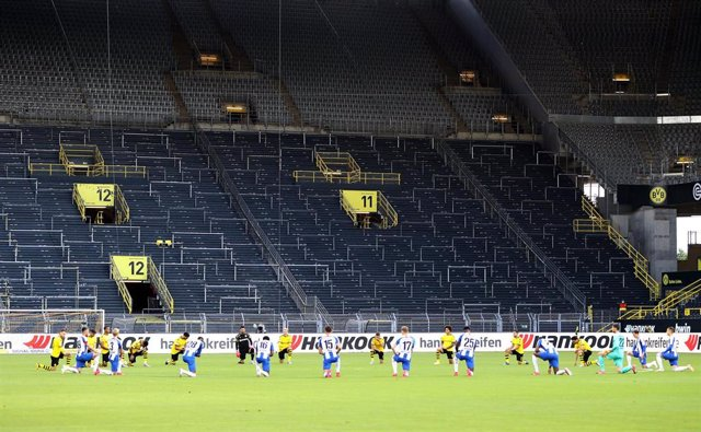 dpatop - 06 June 2020, North Rhine-Westphalia, Dortmund: Players of both teams kneel around the centre circle in solidarity with the demonstrators in the USA, before the German Bundesliga soccer match between Borussia Dortmund and Hertha BSC at Sig nal Id