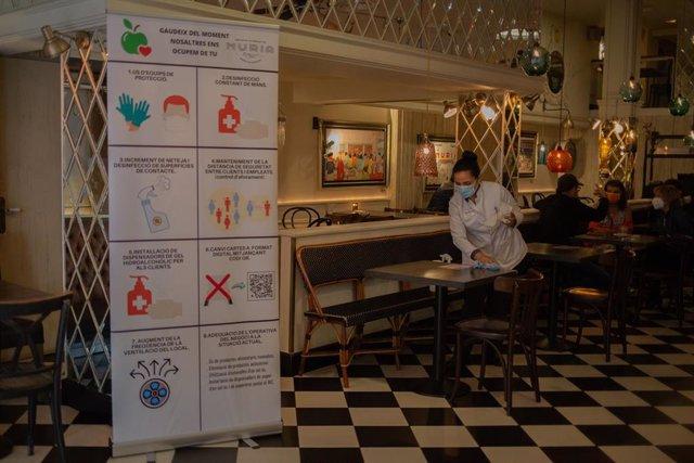 Una camarera limpia una mesa del histórico local barcelonés Núria, que ha simbolizado este lunes por la mañana, con un desayuno popular, la reapertura de bares y restaurantes de La Rambla por el inicio de la Fase 2 de la desescalada por el coronavirus.