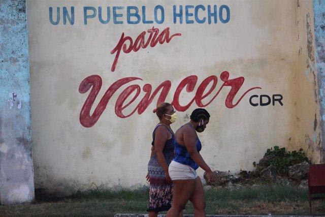 Dos mujeres pasean con mascarilla por una calle de La Habana durante la pandemia de coronavirus