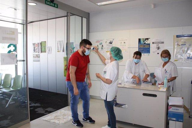 Profesional sanitario toma temperatura  a un paciente