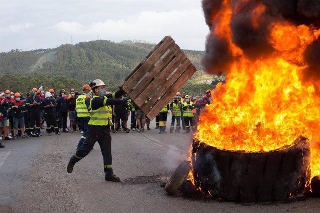 Un participante echa un palé de madera a la barricada realizada a las puertas de la factoría de San Cibrao, donde participantes han quemado de neumáticos, en una nueva manifestación del comité de empresa de Alcoa.