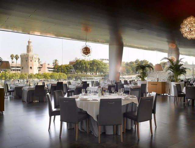 Panorámica interior de una de las salas del restaurante de Abades Triana de Sevilla con vistas a la Torre del Oro