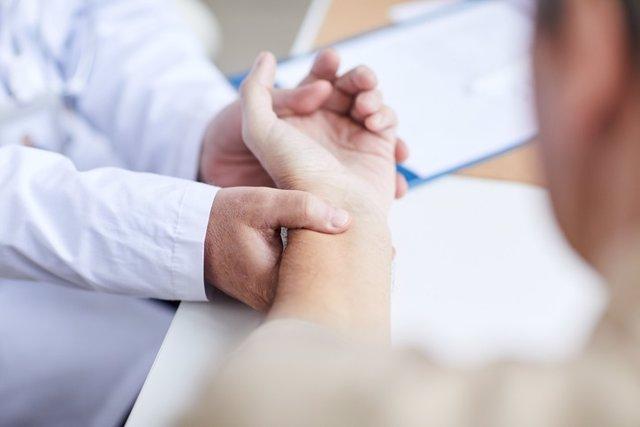 Médico tomando la pulsación a un paciente.