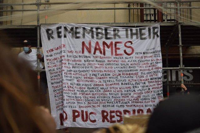 Cartel que recuerda personas que han muerto por racismo colgada en una manifestación antirracista en la plaza Sant Jaume de Barcelona