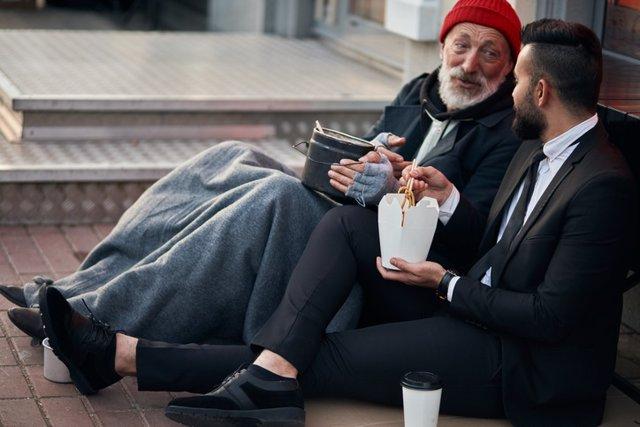 Senior hombre mendigo caucásico contando historia sobre la vida al empresario    Apuesto hombre de negocios en traje sentado en el piso con un hombre sin hogar juntos, escuchar su historia de vida. Contraste a las personas, ricas y pobres, pero no importa